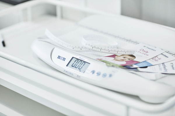 Pile of baby care brochures on scales