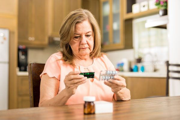 Elderly woman sitting at the table reading her medicine label