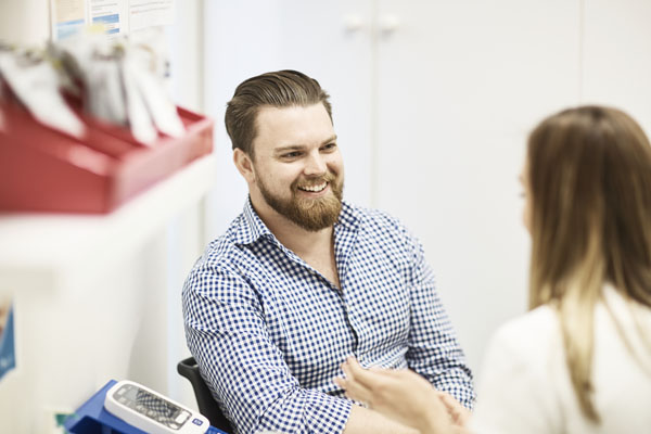 Smiling man speaking with Pharmacist