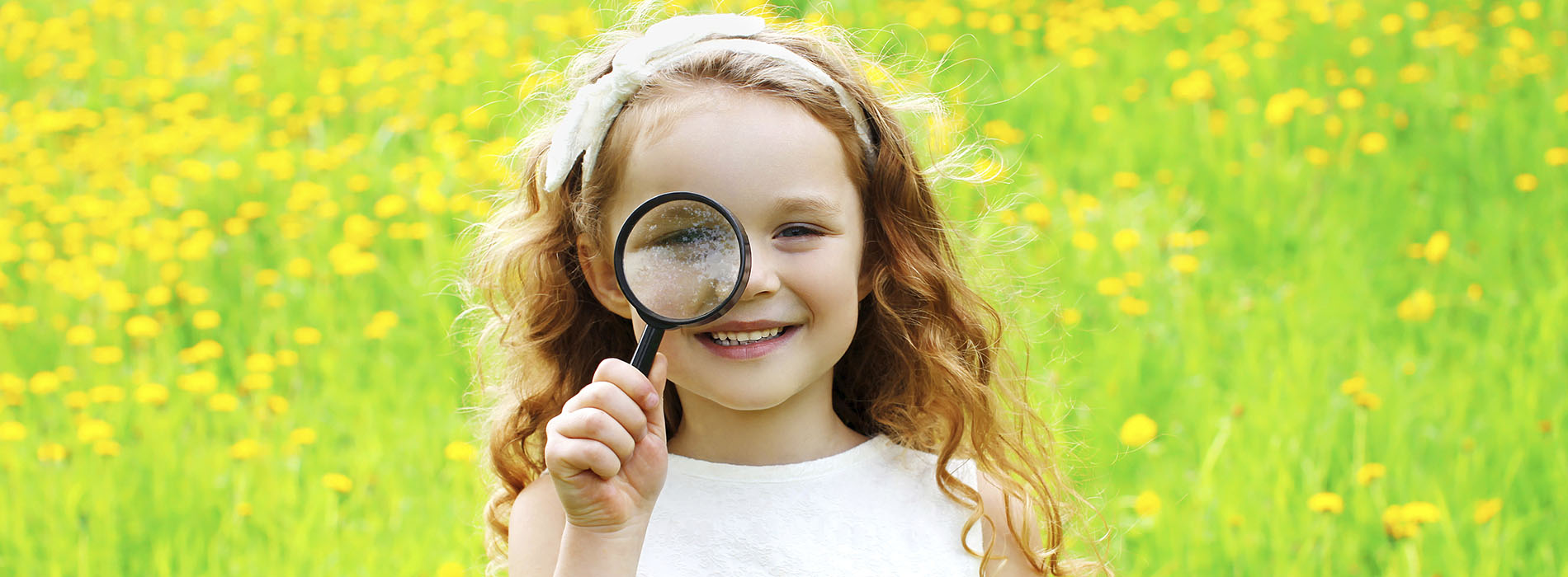Smiling girl standing in a green field, looking through a magnifying glass