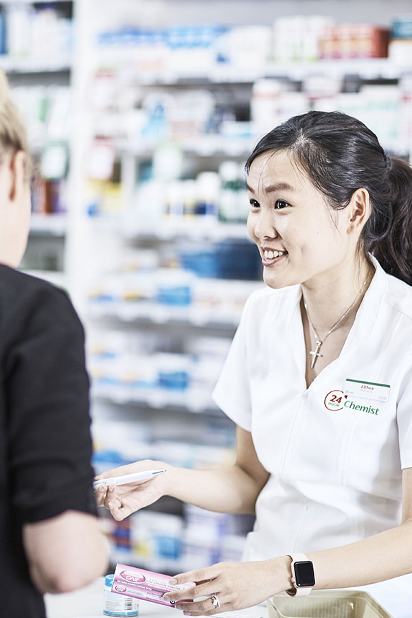 Smiling Pharmacist speaking with customer at shop counter