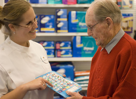 Pharmacist showing a customer a dose administration aid