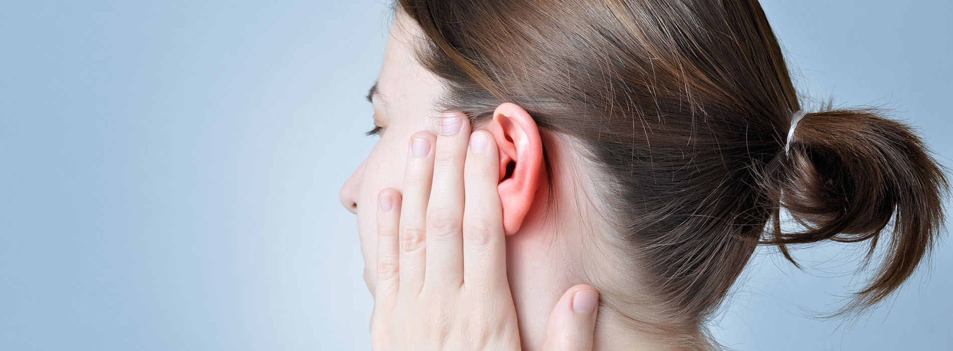 Profile of woman touching her sore ear