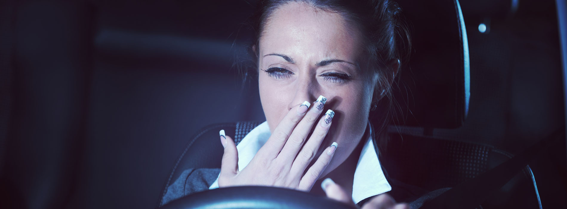 Woman yawning while driving her car