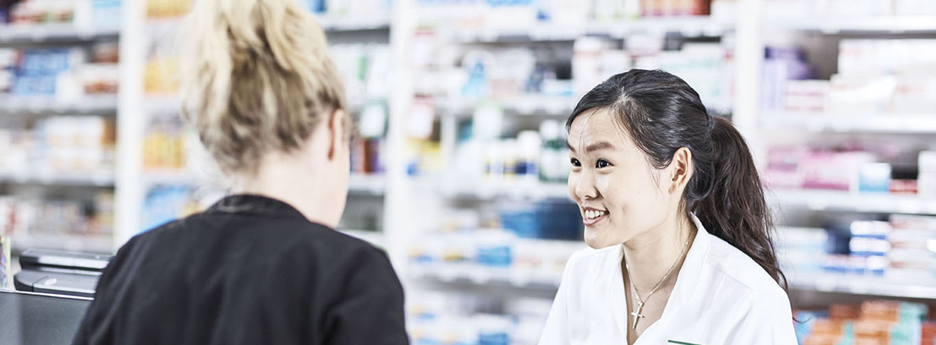 Smiling Pharmacist speaking with a customer at the shop counter